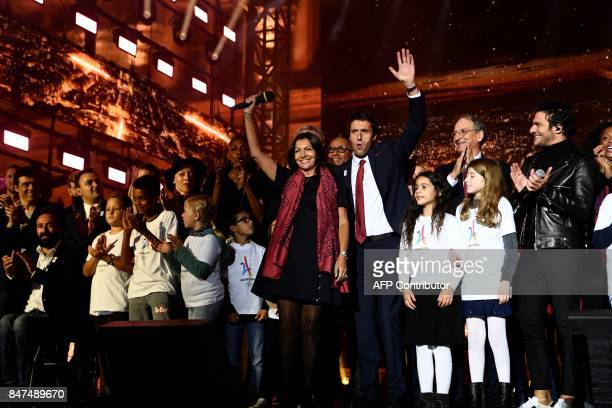 Executive President of the Paris delegation Tony Estanguet and Mayor of Paris Anne Hidalgo waves on stage during a concert in front of the Hotel de...