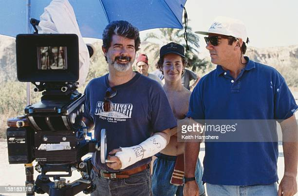 Executive producer George Lucas wearing a plaster cast and a Skywalker Symphony Orchestra tshirt on the set of the television series 'The Young...