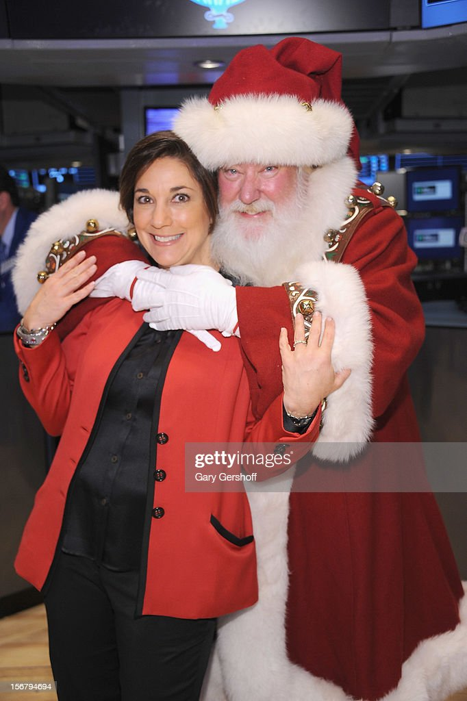 Executive Producer of Macy's Thanksgiving Day Parade, Amy Kule (L) and Santa Claus pose for pictures after ringing the opening bell at the New York Stock Exchange on November 21, 2012 in New York City.