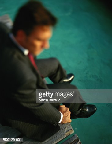 Executive sitting on jetty, elevated view : Stock Photo