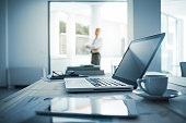 Businessman standing with arms crossed in his office, desktop with laptop on foreground, selective focus