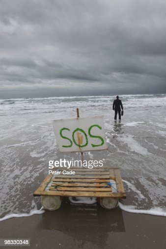 Executive stood in sea, raft washed up on beach