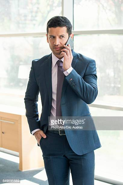 Executive talking on cell phone in office