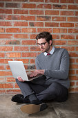Executive using laptop against brick wall in office