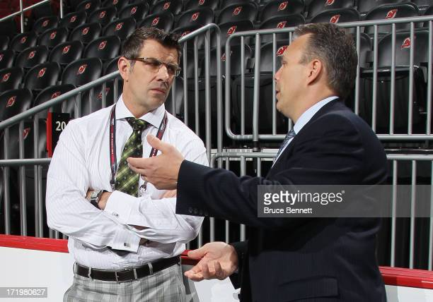 Executive Vice President and General Manager Marc Bergevin of the Montreal Canadiens speaks with Executive Vice President General Manager Kevin...
