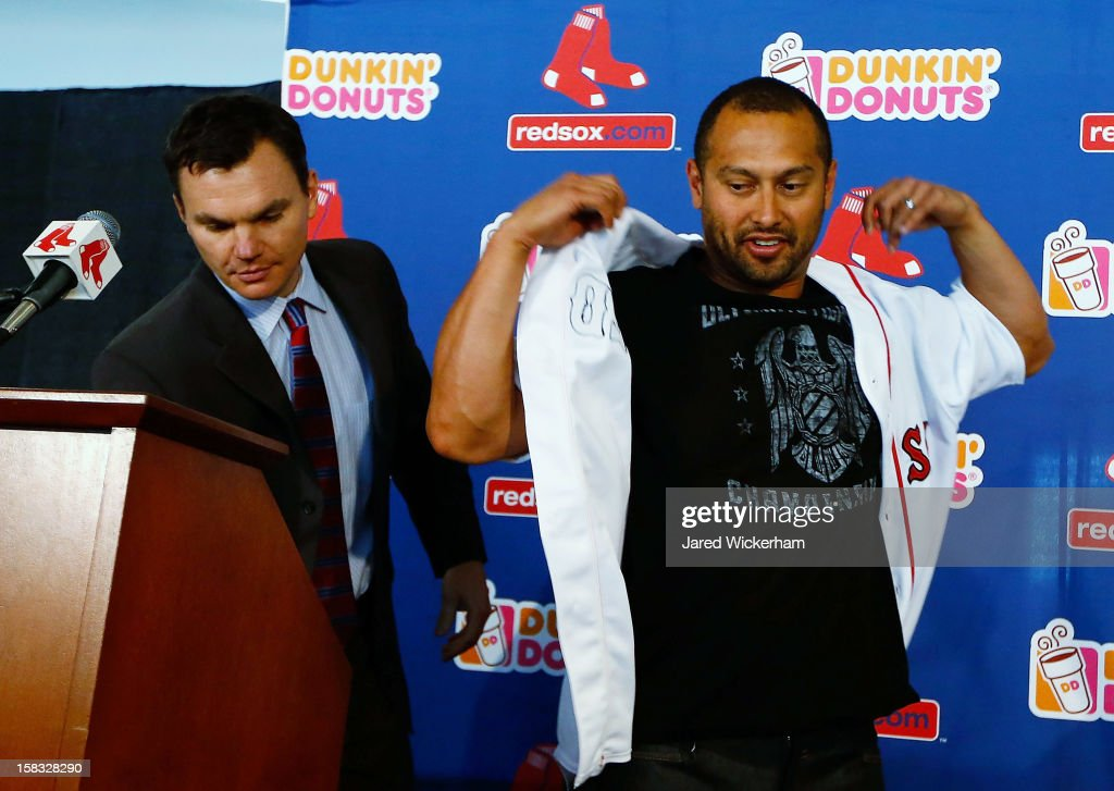 Executive Vice President and General Manager of the Boston Red Sox Ben Cherington (L) looks down as <a gi-track='captionPersonalityLinkClicked' href=/galleries/search?phrase=Shane+Victorino&family=editorial&specificpeople=576251 ng-click='$event.stopPropagation()'>Shane Victorino</a> puts on his jersey, after signing a three-year contract, on December 13, 2012 at Fenway Park in Boston, Massachusetts.