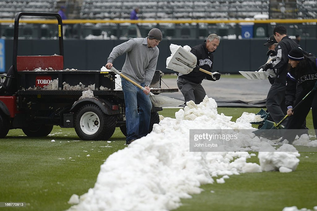 Executive Vice President, Chief Baseball Officer/General Manger Dan O'Dowd helps out shoveling snow from right field. Rockies grounds crew and employees work to clear the field of snow to get the first game of a double header in against the New York Mets April 16, 2013 at Coors Field.