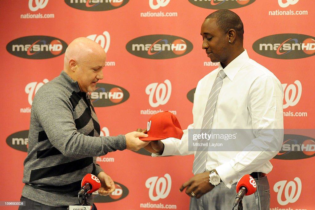 Executive Vice President of baseball operations Mike Rizzo gives Rafael Soriano of the Washington Nationals his new cap during his introduction press conference on January 17, 2013 at Nationals Park in Washington, DC.