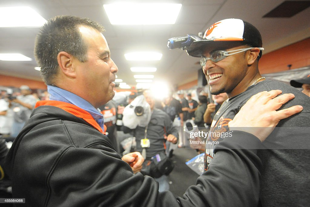 Executive Vice-President of Baseball Operations Dan Duquette (L) and Nelson Cruz #23 (R) celebrate in locker room after the Orioles clinch the American League East Division after a baseball game against the Toronto Blue Jays on September 16, 2014 at Oriole Park at Camden Yards in Baltimore, Maryland.