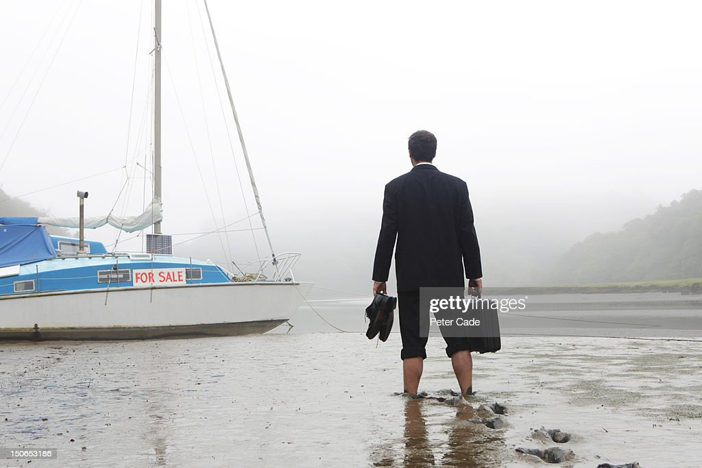 Executive walking in mud towards boat for sale : Stock Photo