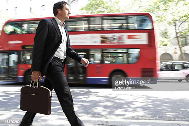 Executive walking on street, red bus passing