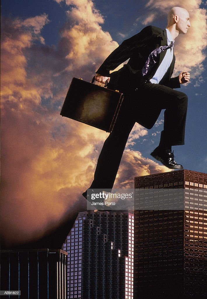 Executive walking on top of buildings : Stock Photo