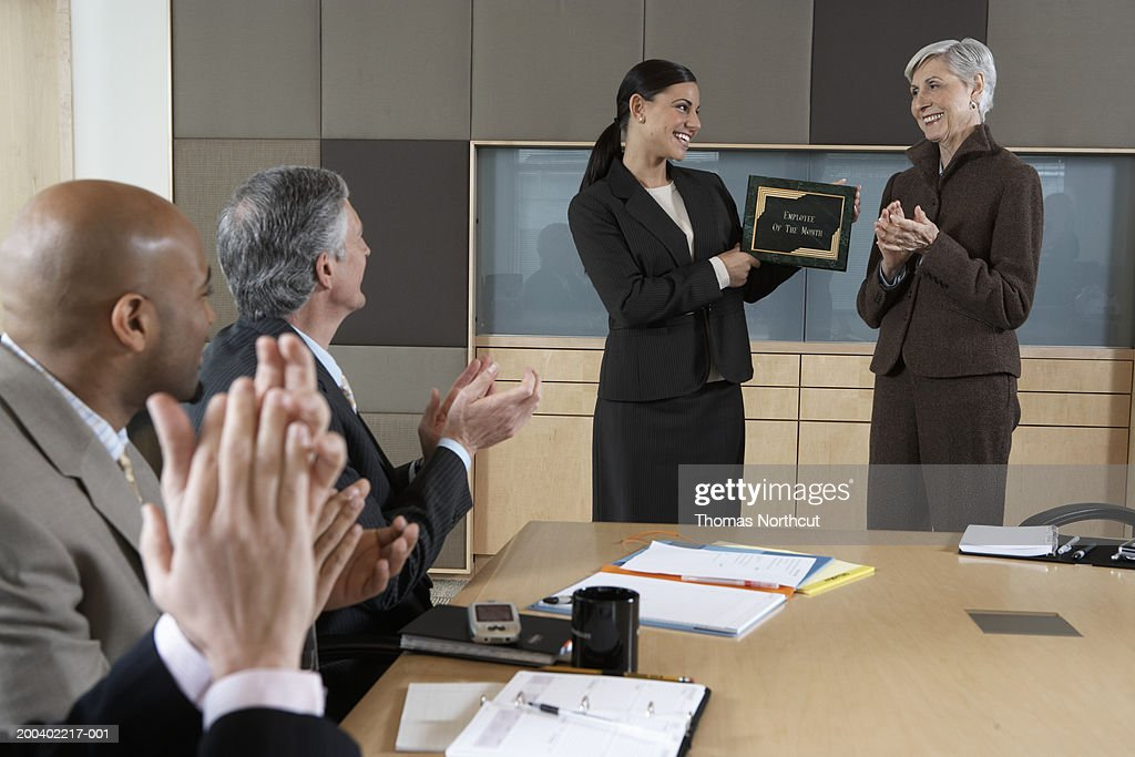Executives applauding for woman holding 'Employee of the Month' plaque