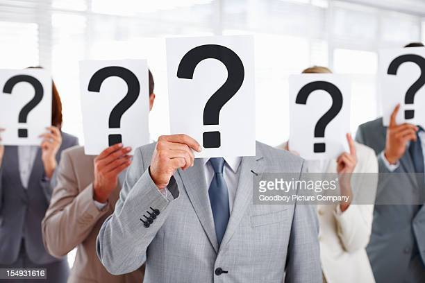 Executives covering their faces with question mark