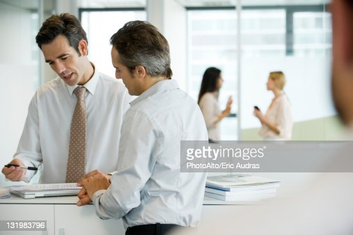 Executives discussing document : Stock Photo