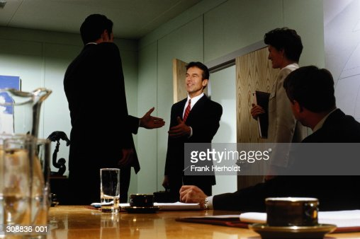 Executives greeting each other in conference room : Stock Photo