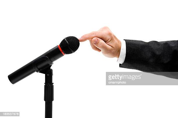 Executive's hand testing wireless Microphone, white background