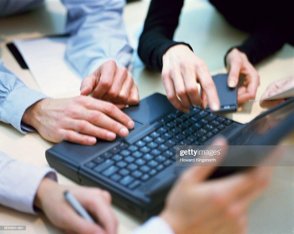Executives' hands around laptop computer, close-up : Stock Photo
