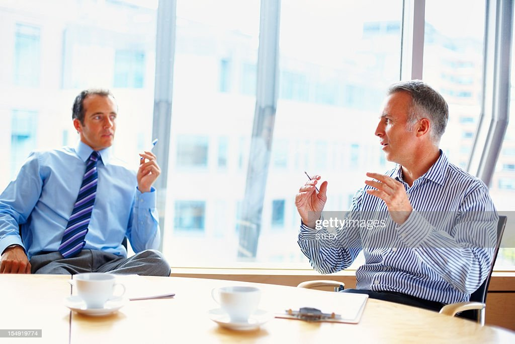 Executives having conversation at table : Stock Photo