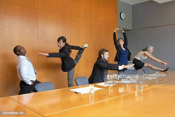 Executives in conference room stretching