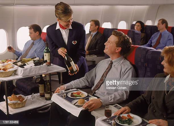 Executives in first class enjoying in-flight meal