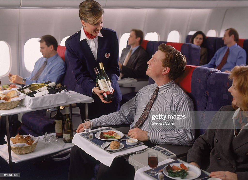 Executives in first class enjoying in-flight meal : Stock Photo