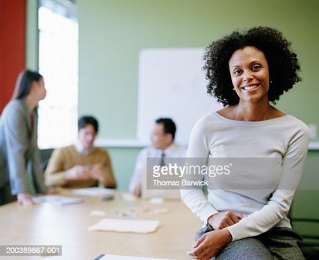 Executives meeting in boardroom (focus on young woman in foreground) : Stock Photo