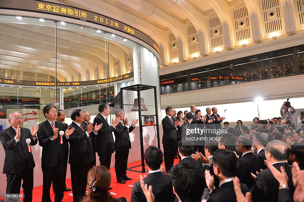 Executives of the Tokyo Stock Exchange (on stage) and guests applaud during a ceremony to celebrate the last trading day of 2012 at the Tokyo Stock Exchange in Tokyo on December 28, 2012. The Nikkei ended the last trading day of the year up 0.70 percent, or 72.20 points, closing at 10,395.18, its best finish since Japan's quake-tsunami disaster in 2011, and up 22.9 percent over the past year.