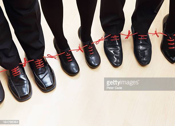 Executives shoes tied together with red laces