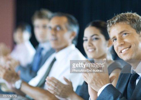 Executives sitting in seminar, clapping