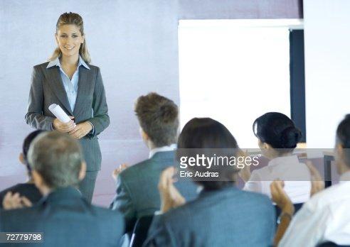 Executives sitting in seminar, woman standing facing group