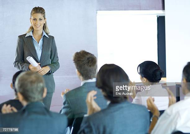 Executives sitting in seminar, woman standing facing group