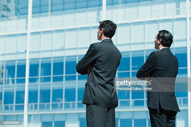 Executives standing by office building with arms folded