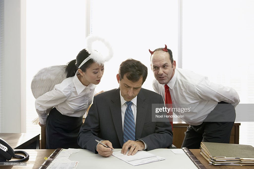 Executives with halo and devil horns standing behind businessman : Stock Photo