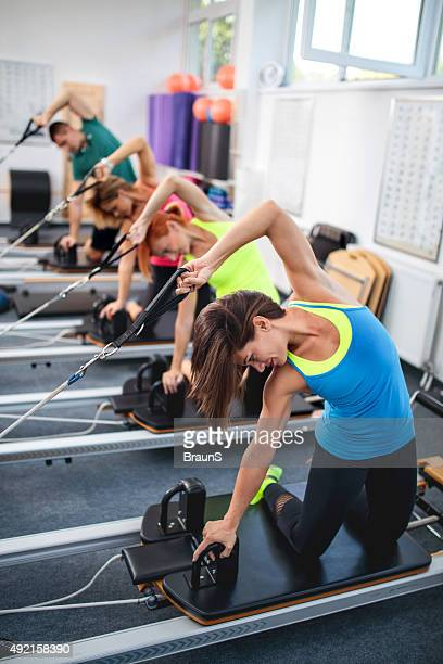 Exercise class on Pilates machines in a health club.