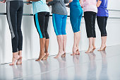 A cropped rear view of a group of six women in a dance studio taking a barre fitness class.  They are unrecognizable, visible only from the chest down.  They are standing in a row on the balls of thei