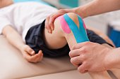 Physiotherapist doing with child exercise for knee