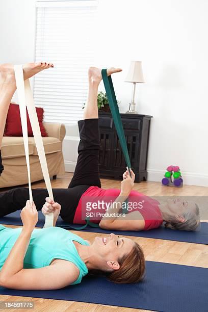 Correa de socios haciendo yoga ejercicios de estiramiento en la sala de estar