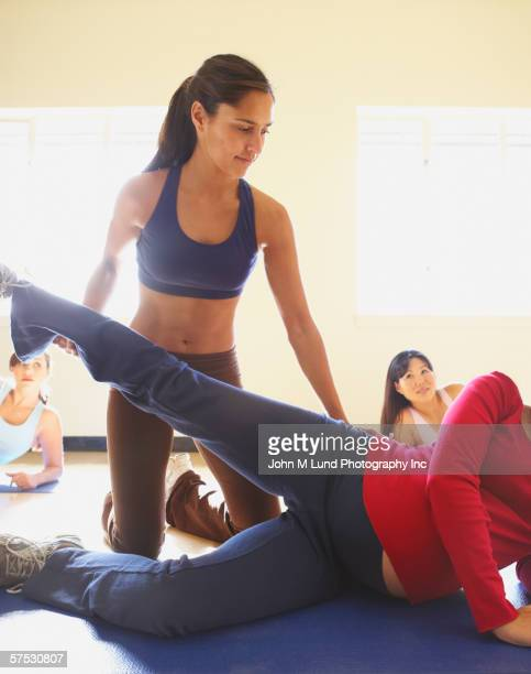 Exercise trainer helping pregnant woman stretch