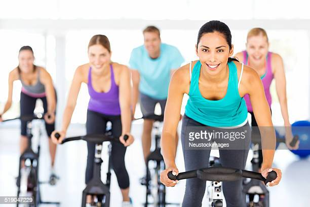 Spinning Class Exercising Together In Gym