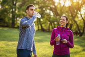 Young couple exercising in park. They are drinking water.