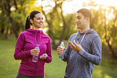 Young couple is talking after exercising in park.