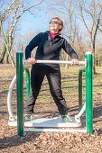 exercising on a machine at the outdoor gym