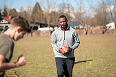 Adult black  man holding a ball for american football and training young male athlete.
