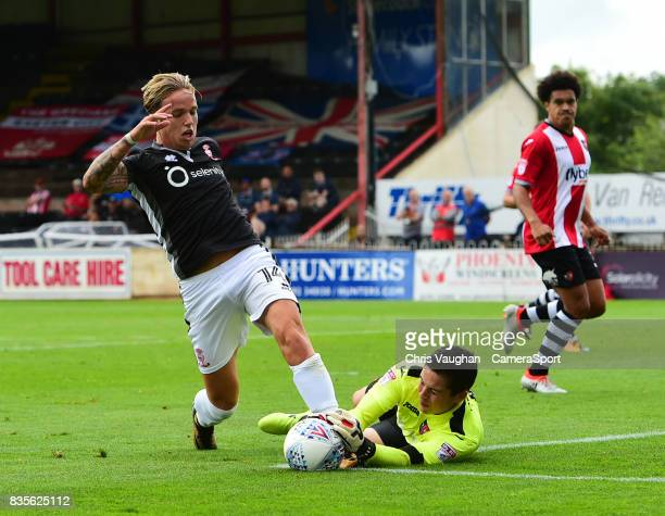 Exeter City's Christy Pym saves at the feet of Lincoln City's Jordan MaguireDrew during the Sky Bet League Two match between Exeter City and Lincoln...