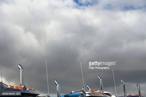 Exhaust pipes of semi-trucks against clouds