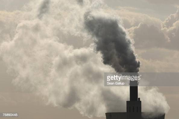Exhaust rises from the main chimneys of the coalfired power plant Heizkraftwerk Reuter West as steam rises from its cooling tower behind July 31 2007...