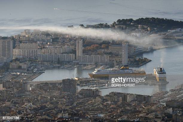 TOPSHOT Exhaust smoke from Corsica Ferries' company hovers above Toulon harbour on November 21 2017 / AFP PHOTO / BORIS HORVAT
