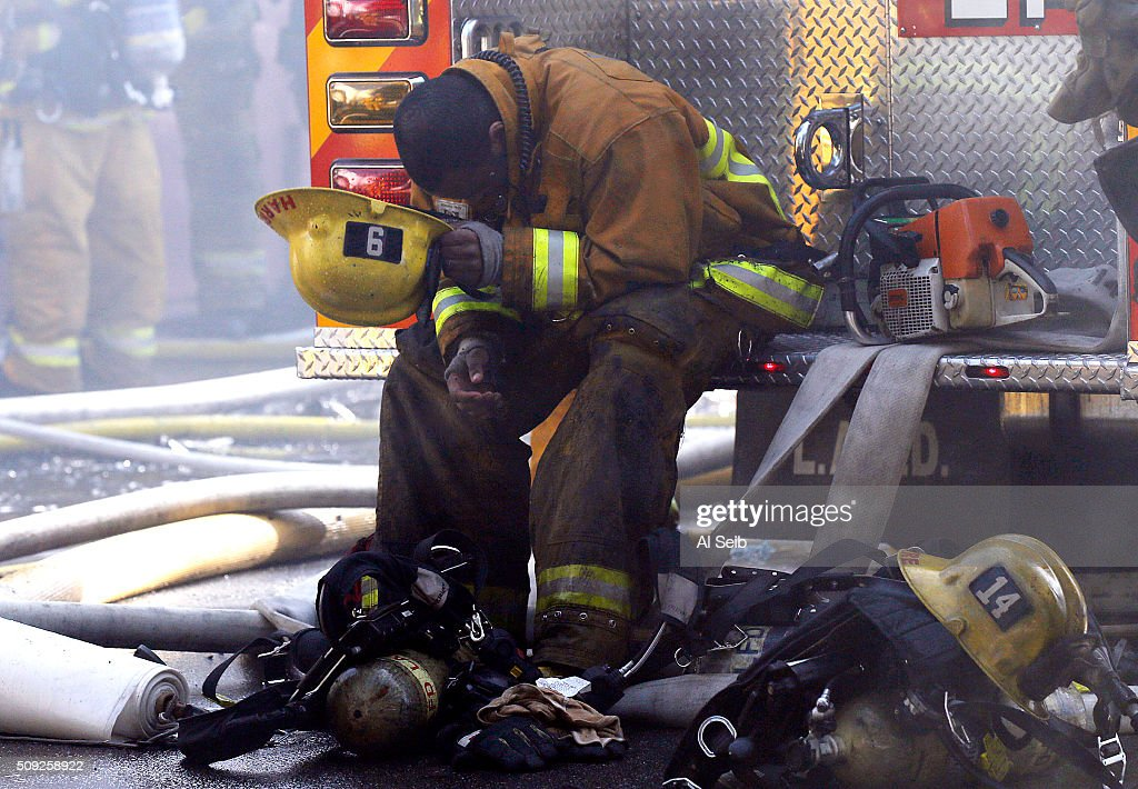 Exhausted a LA City Firefighter takes a momment to catch his breath as Firefighters attack a fire in a small commercial building in the 1300 block of Newton Street near downtown Los Angeles Tuesday morning February 09, 2016. A firefighter fell and suffered minor injuries while battling the blaze.