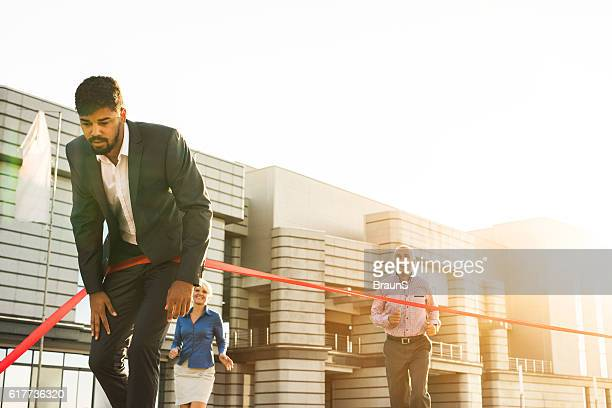 Exhausted African American businessman crossing the finish line.